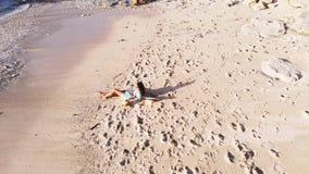 Punto di vista aereo del fuco di giovane donna castana in occhiali da sole che si trovano sulla spiaggia di paradiso e sul telefo archivi video