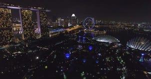 Punto di vista aereo di notte di Supertree e di Marina Bay Sands a Singapore dal fuco stock footage