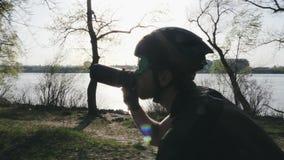 Punto di vista alto vicino del ciclista con l'acqua potabile della barba mentre guidando bici Il Sun splende attraverso gli alber archivi video