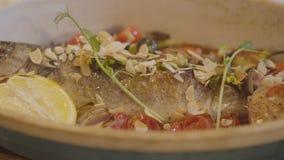 Punto di vista alto vicino del pesce al forno fresco che si trova in piatto profondo decorato con il limone, la ciliegia dei pomo video d archivio