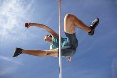 Punto di vista di angolo basso dell'atleta maschio risoluto che salta sopra le transenne fotografie stock libere da diritti