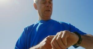 Punto di vista di angolo basso dell'uomo caucasico senior attivo facendo uso di smartwatch su una passeggiata alla spiaggia 4k video d archivio