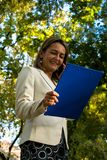 Punto di vista di angolo basso della donna di affari che utilizza telefono cellulare mentre leggendo i documenti nella natura Immagine Stock