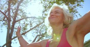 Punto di vista di angolo basso della donna senior caucasica attiva che esegue yoga nel giardino della casa di cura 4k video d archivio