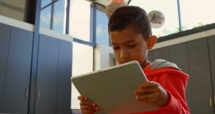Punto di vista di angolo basso dello scolaro asiatico attento che studia con la compressa digitale in aula alla scuola 4k stock footage