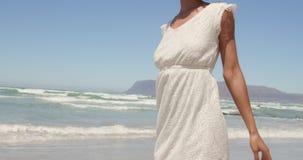 Punto di vista di angolo basso di giovane donna afroamericana divertendosi sulla spiaggia nel sole 4k archivi video
