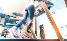 Punto di vista basso della sezione della sportiva attiva che corre sulla pedana mobile allo studio di forma fisica della palestra immagini stock