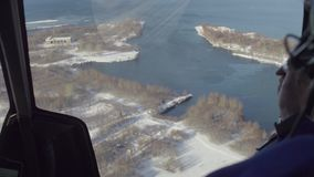 Punto di vista dal pilota di un elicottero che sorvola il villaggio nella foresta e nel lago in Siberia video d archivio