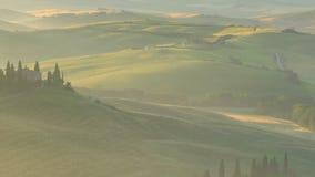 Punto di vista del campo toscano collinoso nebbioso con un'azienda agricola e dei cipressi nell'ora dorata di sera archivi video