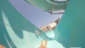 Punto di vista del giovane che fa scorrere giù all'acquascivolo nel aquapark un bello giorno soleggiato Tipo con la macchina foto stock footage