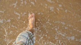 Punto di vista del giovane che fa un passo alla sabbia dorata alla spiaggia del mare Gambe maschii che camminano vicino all'ocean archivi video