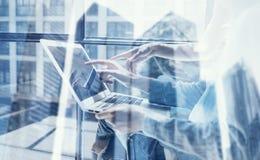 Punto di vista del primo piano del gruppo coworking facendo uso del computer portatile moderno nello studio di progettazione Del  immagini stock libere da diritti