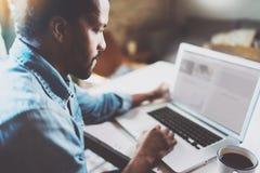 Punto di vista del primo piano dell'uomo africano pensieroso che lavora al computer portatile mentre spendendo tempo a casa Usand immagini stock libere da diritti