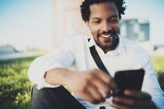 Punto di vista del primo piano dell'uomo africano sorridente dei giovani che invia indicando dito sullo smartphone mentre sedendo Fotografie Stock