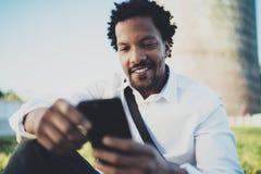 Punto di vista del primo piano dell'uomo africano sorridente dei giovani che invia messaggio di testo dallo smartphone mentre sed Fotografia Stock