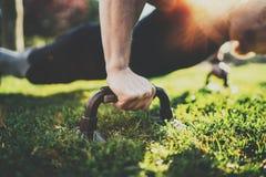 Punto di vista del primo piano dell'uomo bello di sport che fa i piegamenti sulle braccia nel parco sulla mattina soleggiata Conc immagini stock libere da diritti