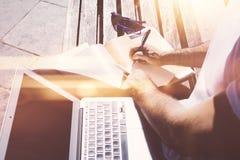 Punto di vista del primo piano dell'uomo che si siede sul banco e che fa le note sul libro di testo Studiando all'università, pre Fotografia Stock