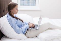 Punto di vista del primo piano della donna che per mezzo del computer portatile sul suo letto Fotografia Stock