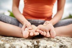 Punto di vista del primo piano della donna che si siede nella posa del loto di yoga sulla roccia sopra il fiume Immagine Stock Libera da Diritti