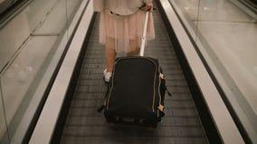 Punto di vista del primo piano della giovane donna con la valigia che sta sulla scala mobile in aeroporto Femmina dei pantaloni a fotografia stock libera da diritti