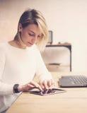 Punto di vista del primo piano di giovane bella donna che lavora alla tavola di legno Compressa commovente della mano femminile s Fotografia Stock