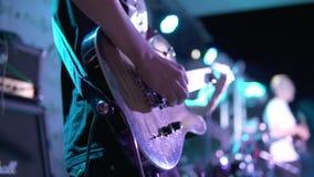Punto di vista del primo piano di un uomo che gioca chitarra elettrica in scena al concerto Colpo lento video d archivio