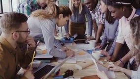 Punto di vista del primo piano di giovane gruppo di affari che lavora insieme vicino alla tavola, confrontante le idee Due equipa video d archivio