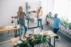 punto di vista dell'angolo alto dei colleghi multietnici felici di affari che ballano e che si divertono in moderno immagini stock libere da diritti