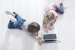Punto di vista dell'angolo alto del fratello e della sorella che per mezzo del computer portatile sul pavimento a casa fotografie stock
