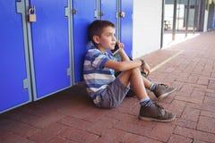 Punto di vista dell'angolo alto del ragazzo che parla sul telefono cellulare mentre sedendosi dagli armadi Immagini Stock Libere da Diritti