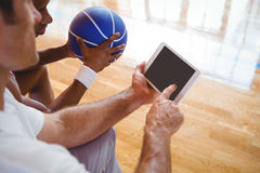 Punto di vista dell'angolo alto dell'allenatore che mostra compressa digitale al giocatore di pallacanestro Fotografia Stock Libera da Diritti