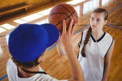 Punto di vista dell'angolo alto dell'allenatore maschio che forma giocatore di pallacanestro femminile Fotografia Stock Libera da Diritti