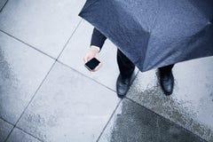 Punto di vista dell'angolo alto dell'uomo d'affari che tiene un ombrello e che esamina il suo telefono nella pioggia Fotografia Stock
