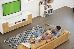 Punto di vista dell'angolo alto della famiglia che si siede su Sofa In Lounge Watching TV Immagine Stock Libera da Diritti