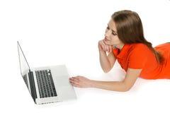 Donna che si trova sul pavimento con il suo computer portatile Fotografia Stock Libera da Diritti