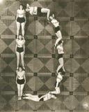 Punto di vista dell'angolo alto delle donne che formano la lettera D immagini stock