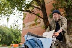 Punto di vista dell'uomo senza tetto che cammina spingendo carrello Immagini Stock Libere da Diritti