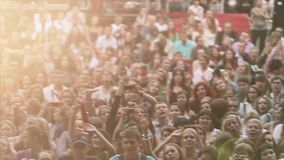 Punto di vista della gente incoraggiante al concerto in tensione di estate Banda di musica che esegue in scena folla Fasci di Sun video d archivio