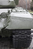 Punto di vista della parte anteriore del trattore a cingoli verde del carro armato che sta sulla terra con il primo piano delle r Fotografie Stock