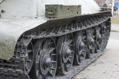 Punto di vista della parte anteriore del trattore a cingoli verde del carro armato che sta sulla terra con il primo piano delle r Fotografia Stock