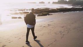 Punto di vista della parte del tipo in vestiti alla moda con le passeggiate dello zaino lungo la spiaggia di sabbia nera, movimen video d archivio