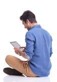 Punto di vista della parte posteriore del lato di un uomo che lavora al computer della compressa fotografie stock libere da diritti