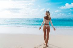 Punto di vista della parte della ragazza con bottino in bikini beige di colore che riposa sulla spiaggia abbandonata immagini stock