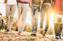 Punto di vista delle gambe degli amici che camminano nel parco della bici della città con la lampadina fotografia stock