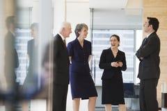 Punto di vista delle persone di affari che sorridono e che conversano nella a Immagini Stock Libere da Diritti