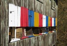 Punto di vista dettagliato di vecchia arnia variopinta di legno e delle api di volo Immagine Stock Libera da Diritti