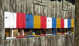 Punto di vista dettagliato di vecchia arnia variopinta di legno e delle api di volo che portano miele Immagini Stock Libere da Diritti