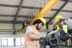 Punto di vista di angolo basso dei lavoratori manuali che lavorano al macchinario nell'industria metalmeccanica fotografie stock libere da diritti