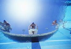Punto di vista di angolo basso dei nuotatori femminili pronti a tuffarsi stagno dalla posizione di partenza Fotografia Stock