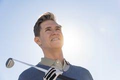 Punto di vista di angolo basso del club di golf della tenuta dell'uomo contro il cielo Fotografie Stock